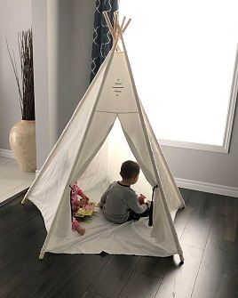 Ryker and Vienna in a white teepee about six feet tall, both reading books. The teepee is set up on a dark laminate floor in their living room