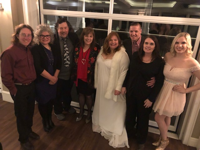 Bride Loreena in a beautiful, long white gown and faux-fur coat surrounded by producer Ryan and his wife Wendy, Derek and me, Ken and his wife Nora, and young Sara MeshMesh, the current newscaster on CJBK.