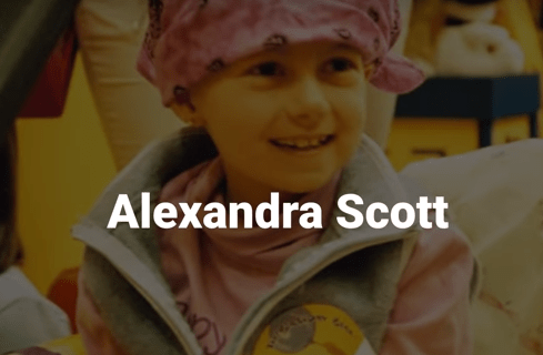 screen snip showing a young girl in a bathrobe and head covering, obviously in a hospital and suffering from cancer, with the name Alexandra Scott below her