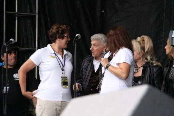 Dennis DeYoung, Leigh Robert and I in close proximity, looking like we are in a conversation. Microphones and other equipment is on the stage, ready for a performance.