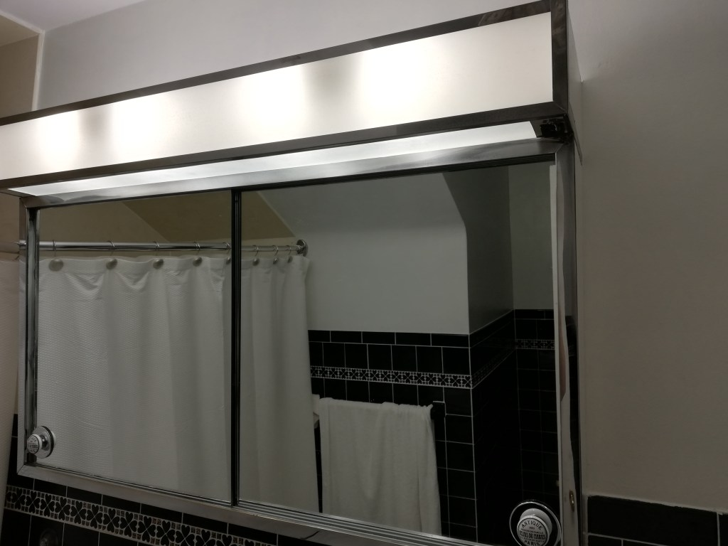 huge medicine cabinet has mirrored doors. Light overhead appears to be florescent but isn't