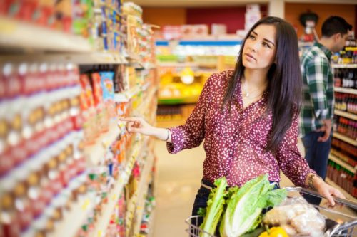 woman selecting a can from a packed grocery store shelf
