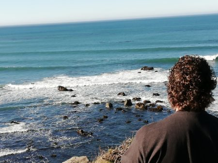 The back of Derek's head in the foreground with mid-size waves crashing into rocks along the Oregon coast in the background