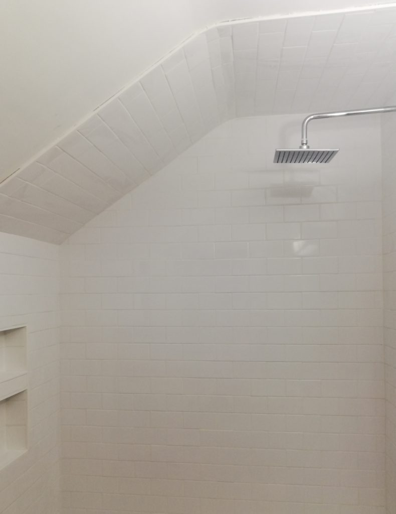shower is tiled with white subway tiles and grouted white, with a cubby with two shelves at the back, also tiled