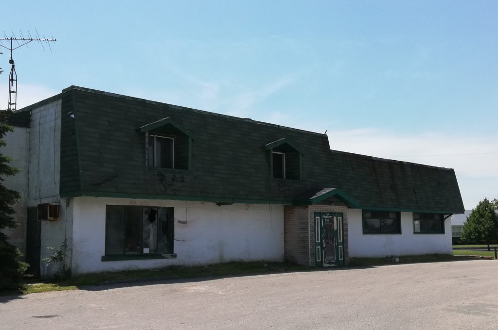 ugly old white building with a black, overhanging roof, with smashed-in windows and chipping paint