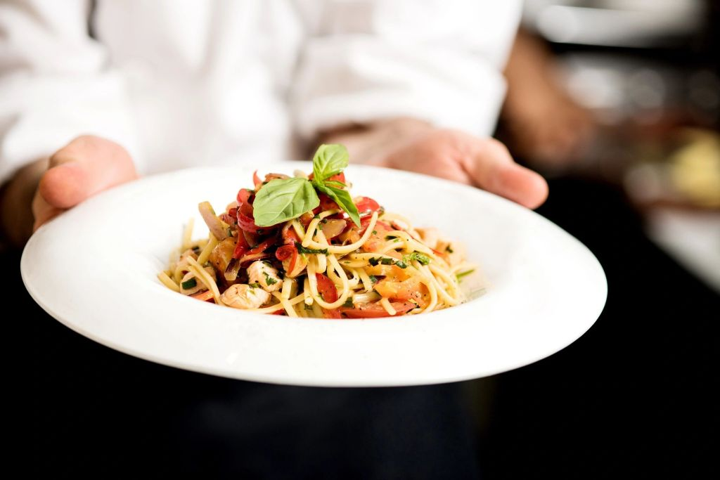 A waiter holds a white bowl full of spaghetti with red sauce and a bay leaf on top