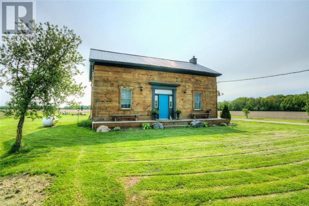 Cute cottage with barnwood on the front, a metal roof and bright blue front door, with freshly mowed grass.