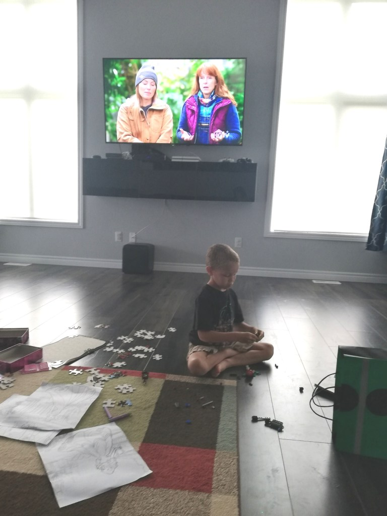 Ryker on the livingroom rug with Lego pieces strewn all over and a couple of them in his hands.