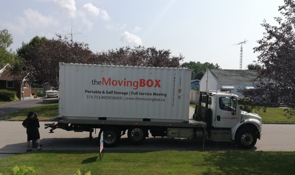 Full shot of the Moving Box seacan on a flat bed truck. Derek and the driver are discussing where it will be placed. It's white with orange and black lettering and 20 feet long.