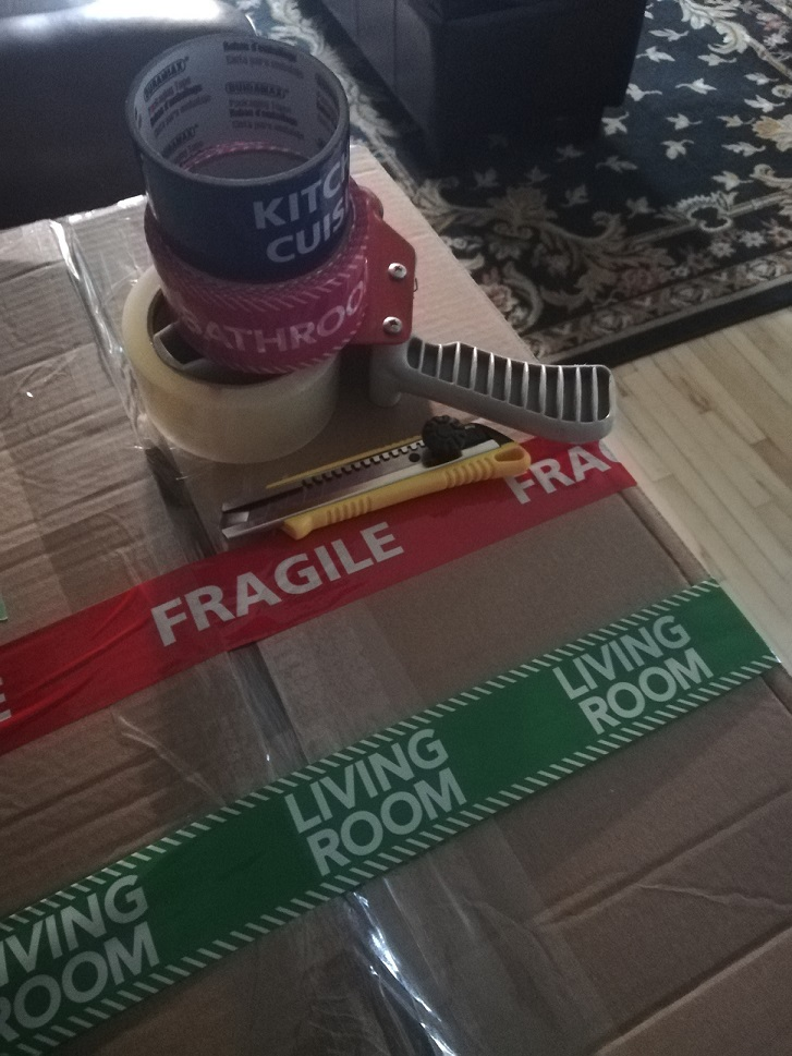 Rolls of tape reading KITCHEN and BATHROOM on top of a tape gun with packing tape. A box cutter. All on top of a packed box with tape across it - red tape reading FRAGILE and green tape reading LIVING ROOM.