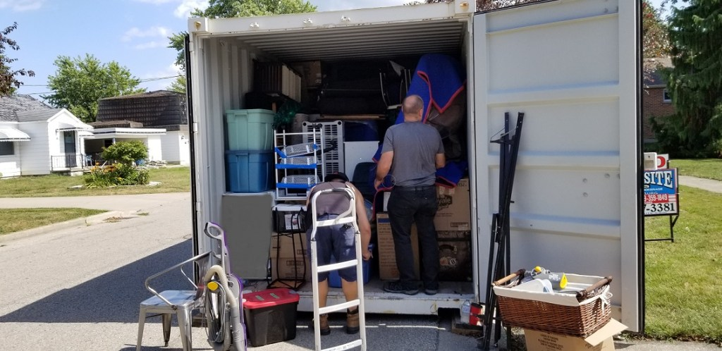 Open end of shipping container with two men inside. There's barely enough room for them to stand inside the end. One man considers where can put something. Another is lifting a box.