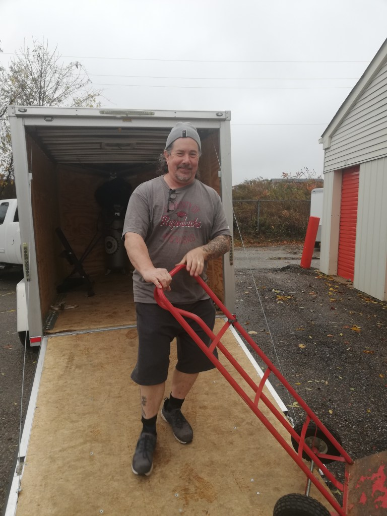 Derek is wearing a wool toque, grey T-shirt, grey shorts, black socks and grey sneakers as he rolls a dolly cart off the trailer ramp.