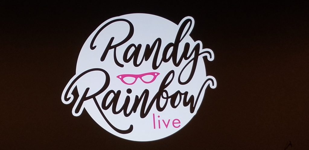 A huge white disc that reads Randy Rainbow live and includes his logo of fuschia cats-eye sunglasses.