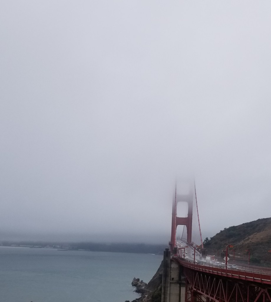 A partial shot of the Golden Gate bridge whose top is obscured by fog.