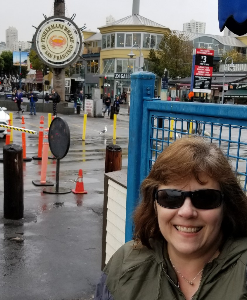 I'm smiling in front of a sign that reads Fisherman's Wharf of San Francisco while people busily mill about and walk past in the background.