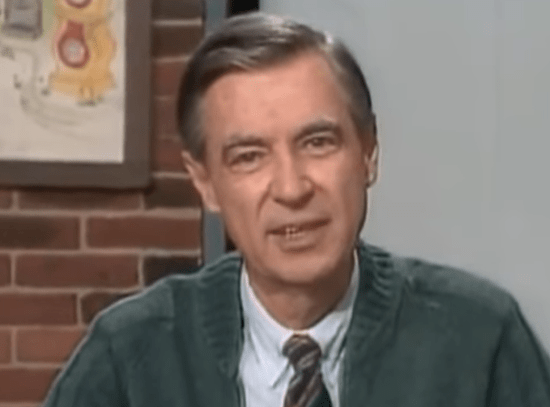 screen grab of Mr Rogers looking into the camera. He's wearing a grey cardigan
