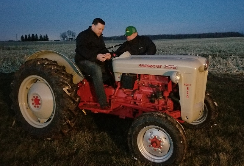 Colin sits on the tractor and looks seriously at the steering column as Rob, standing beside the beast, shows him how it works.
