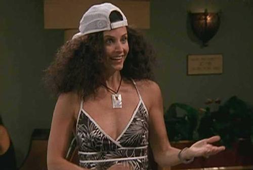 Courteney Cox as Monica Geller on Friends with huge, frizzy hair and wearing a white ball cap.