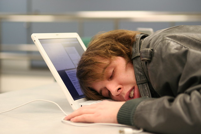 woman with her head on her open laptop, sleeping