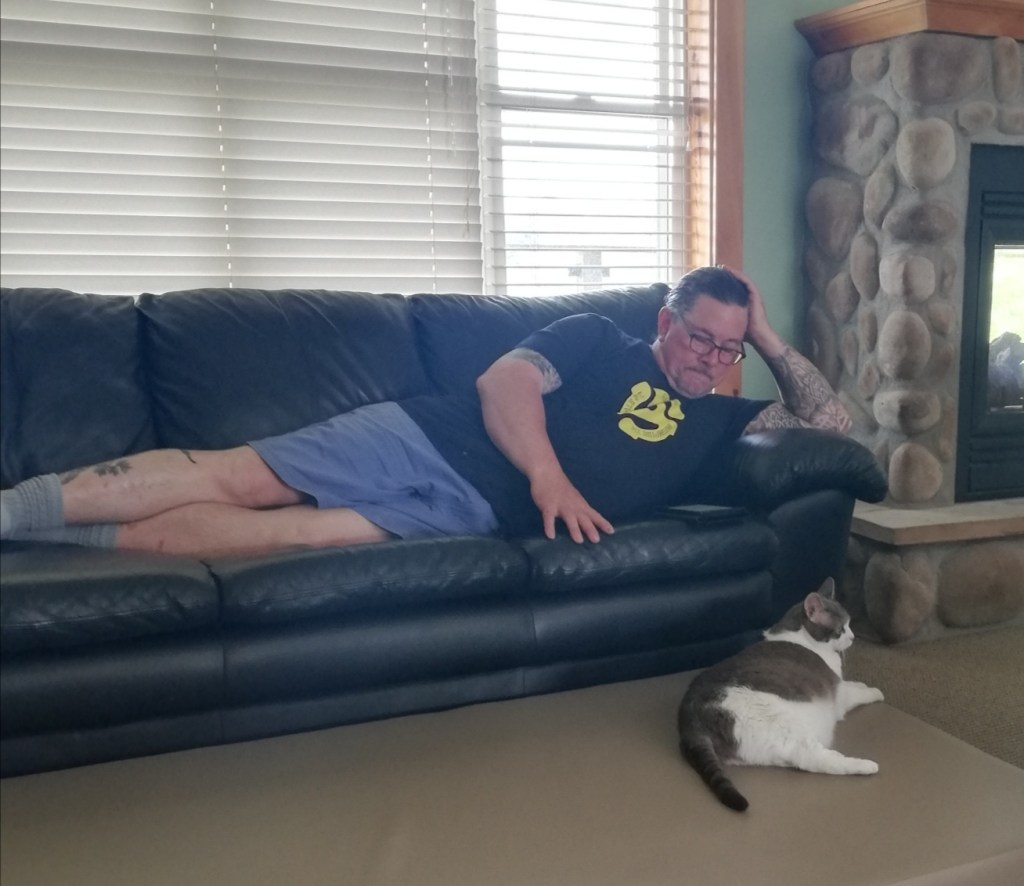Derek lying on a leather couch beside a huge stone fireplace, reading his Kobo, while Sugar relaxes below him on the floor.