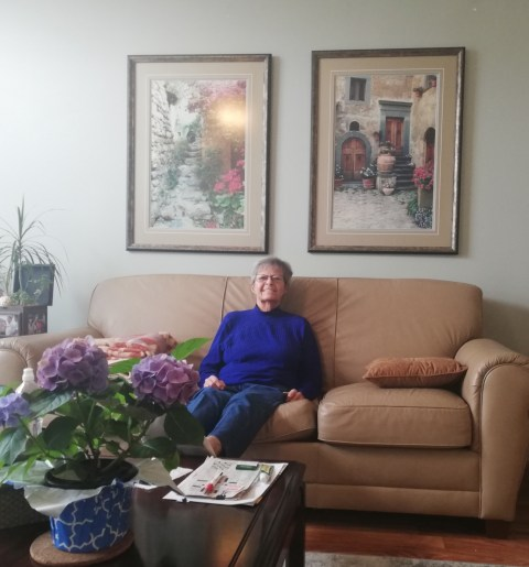 My little Mom looking tiny in a blue sweater and jeans sitting on a tan leather couch below two big framed posters of doorways in Italy