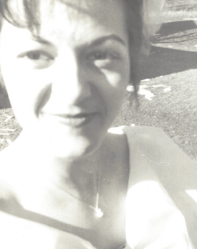 A black and white closeup of my Mom dressed up, with her hair up, smiling slightly and looking beautiful with dark hair and eyes.