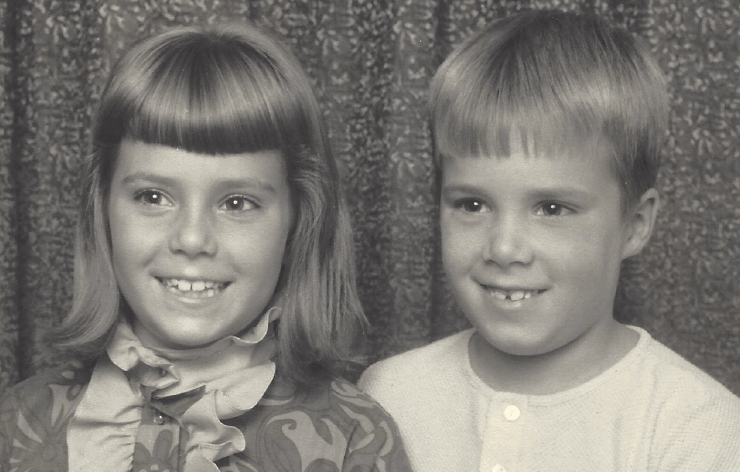 A black and white photo of Kevin and I as little kids, all dressed up and smiling in a professional portrait.