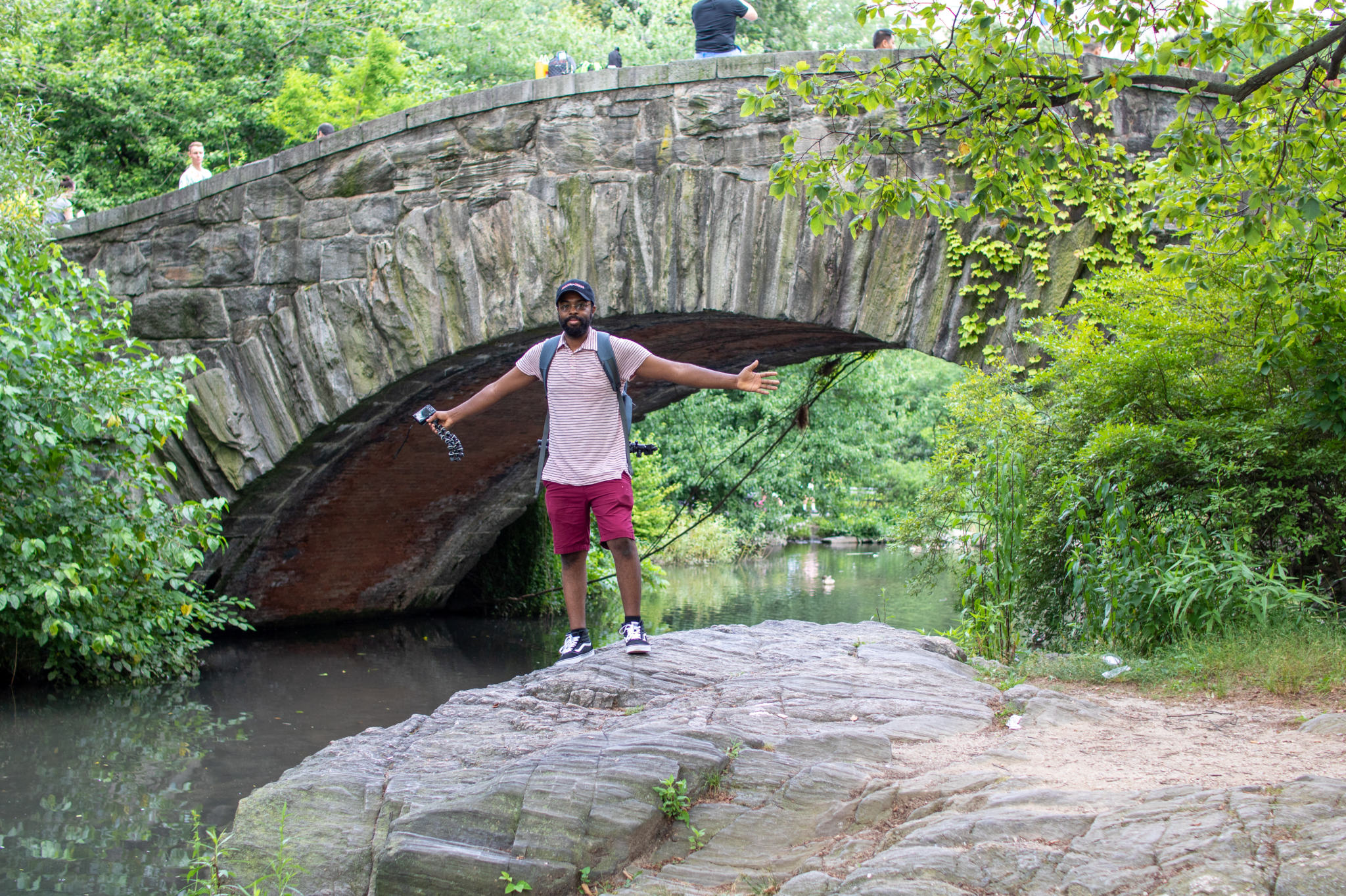 Chris standing on top of a rock in from of gapstow bridge in central park NY