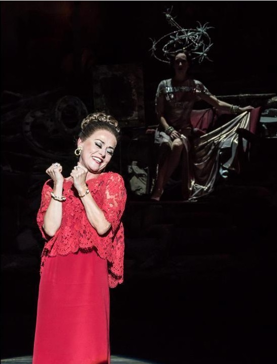 Tracie Bennett as Carlotta Campion. Photo by Johan Persson. In the foreground is the old Carlotta under a bright light in a tasteful red dress. In the background in dim lighting young Carlotta sits gracefully in a silver dress and stared crown.