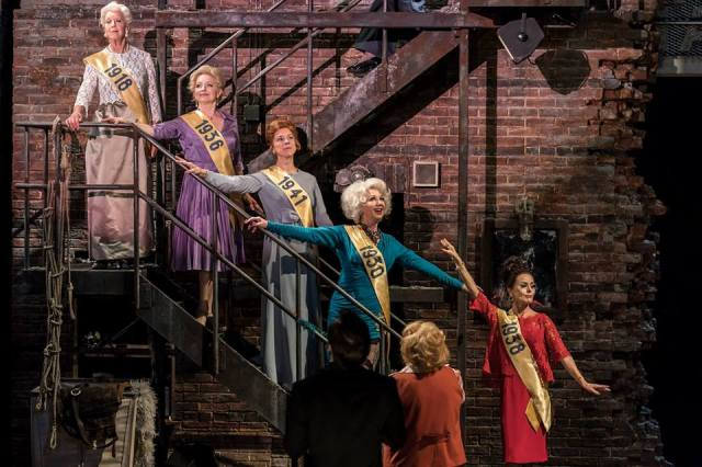 Josephine Barstow, Gemma Page, Janie Dee, Geraldine Fitzgerald and Tracie Bennett. Photo by Johan Persson. Five old women decend on a metal fire escape staircase attached to a crumbling brick wall. They are mostly happy. Each with a sash with the year they performed. 1918,1930,196,1938,1941. In the foreground is another old woman and her husband.