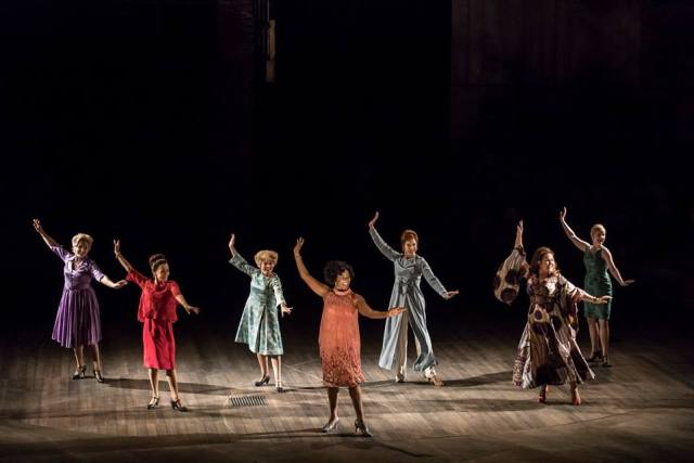 Photo by Johan Persson. Seven of the old Follies tap dance in formation. Arms in the air, toes pointed out.