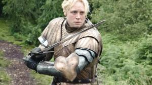 Image shows Gwendoline Christie, the tall woman with chin length blonde hair, as Brinne of Tarth. She wears a suit of golden armour and holds her sword ready to strike someone off screen.