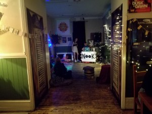 photo of a deceptivly empty bar. Fairy lights on the walls and blankets and pillows on the floor. a dj decks in the backround