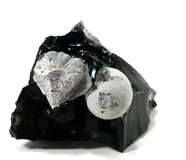 Cristobalite spheres formed via devitrification, loss of silica, from the obsidian matrix (5.9×3.8×3.8 cm) from the Monterey Formation, California, USA (Wiki).