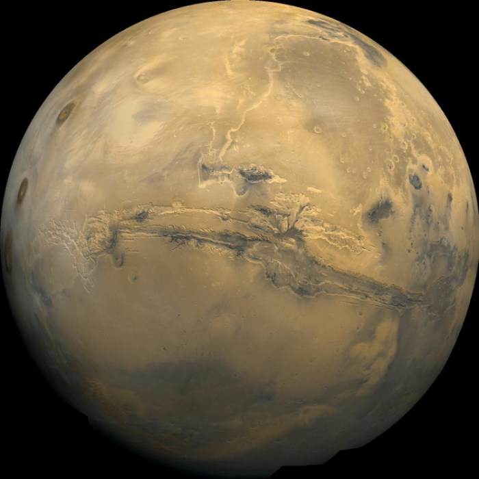 "View of Mars centered on Valles Marineris, a 4,000 km long and 7 km deep canyon slightly longer than the width of the United States. The canyon is thought to have formed as the planet cooled and is possibly as close to plate tectonics as Mars ever got. Visible to the left are three giant shield volcanoes (bottom to top); Arsia Mons with its 110 km in diameter summit caldera, Pavonis Mons and Ascraeus Mons. Because these align on a straight line, it has been suggested that they may be the result of plate tectonics. But as the ""chain"" is over 1,500 km long with no other signs of continental drift such as Martian Alps or Himalayas, as they also have similar ages and do not form a time sequence like the Hawaiian-Emperor Seamount chain on Earth, this is probably incorrect. (NASA)"