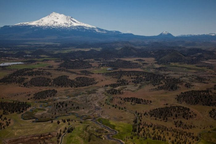 The landscape left by the gigantic flank collapse and subsequent debris avalanche dated to between 300 and 380 kA. The peaks of Shasta and Shastina tower above the landscape and to the right Black Butte right at the foothills of Shasta is clearly visible. (John Scurlock, pbase.com)