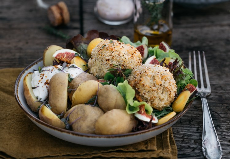 Dinner im Garten: Käse-Blumenkohl Bällchen mit gesottenen Kartoffeln und knackigem Salat. Dazu ein fruchtiger Schnitz frische Feige. Käse-Blumenkohl Bällchen und Kartoffeln angerichtet in einer weissen Bowl auf einem Holztisch. Im Hintergrund ist ein Holzbrett und ein Glas mit Salz sichtbar. Außerdem steht eine Schüssel mit Kartoffeln und Blumenkohl-Käse Bällchen auf dem Tisch.