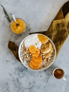 Pances in einer Schüssel mit Müsli und Mandarinenscheiben. Garniert mit Mandeln, Joghurt und Apfelmus. Im Hintergrund steht eine Tasse Espresso und ein Glas Apfelmus. Heller Marmor Untergrund.