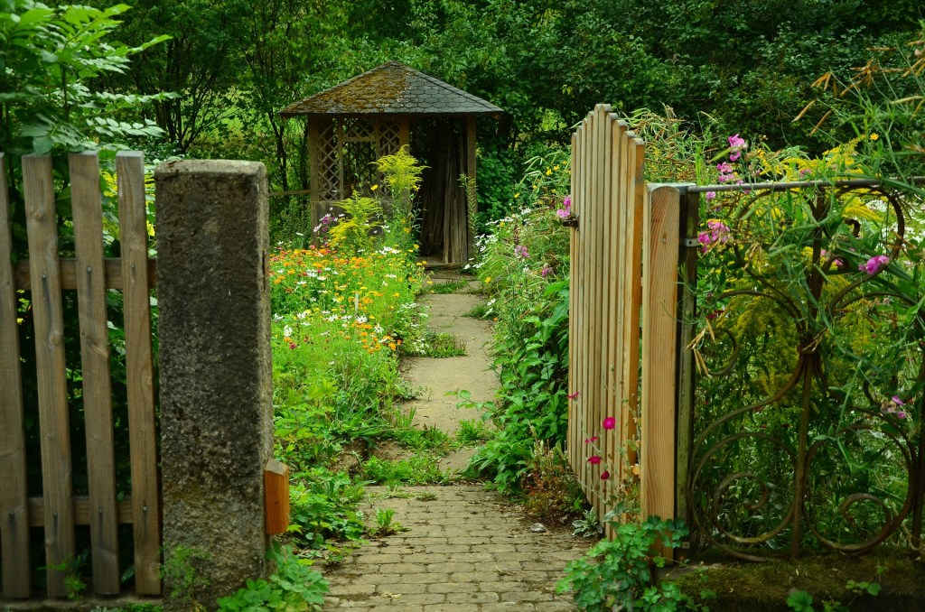 Open gate into a garden of wildflowers and a small cottage