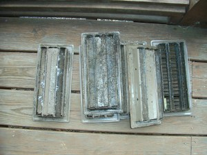 Volunteer Mold Photo shows the back (underside) of HVAC floor vents with large areas of mold growth.