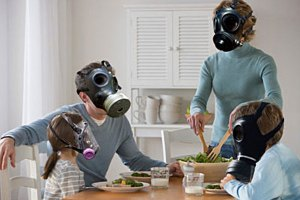 Photo of a family (Husband, Wife, young boy and girl) sitting at the dinner table wearing gas masks.