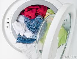 Photo of a slightly ajar laundry machine full of laundry.