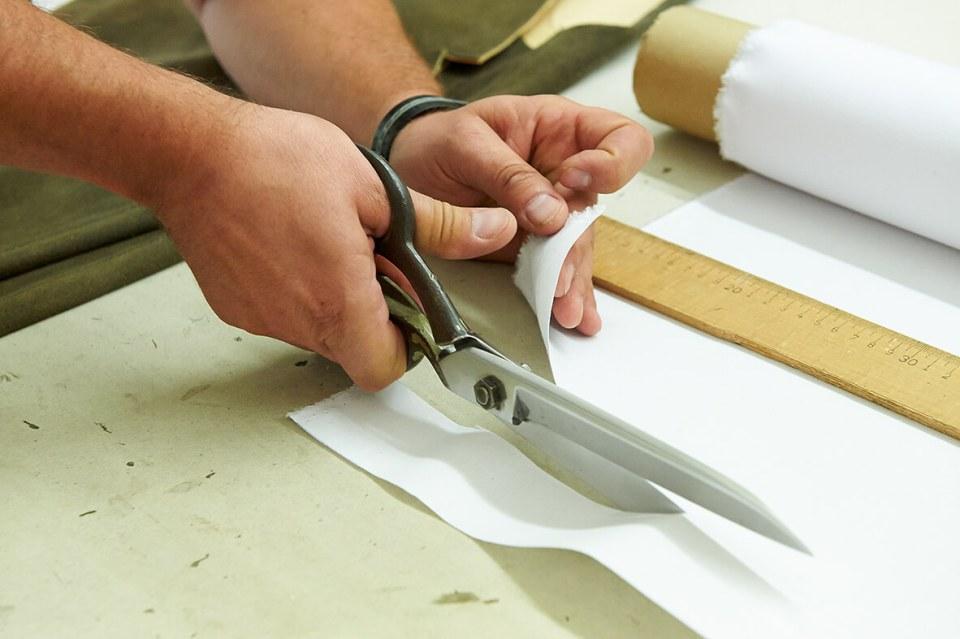 VONsociety: Nahaufnahme von den Männerhänden. Die rechte Hand hält eine Zuschneideschere und schneidet ein Stück von weißem Molino ab.