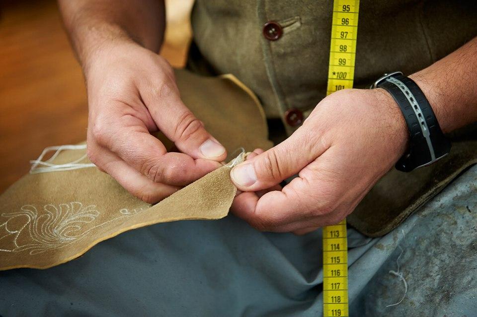 VONsociety: Nahaufnahme eines Seglers. Er hält auf dem Schoß ein Hirschlederteil und ist ist gerade dabei eine Stickerei mit beigem Faden darauf anzufertigen