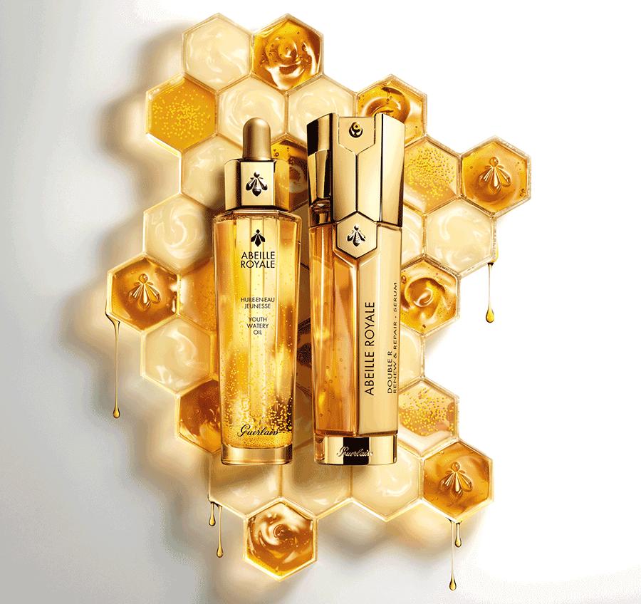 VONsociety: Produktbild der Pflegeline Abeille Royale, Flakon Youth Water Oil  und Double R-Renew & Reparier Serum, im Hintergrund Bienenwaben mit Wachs und Gelee Royal