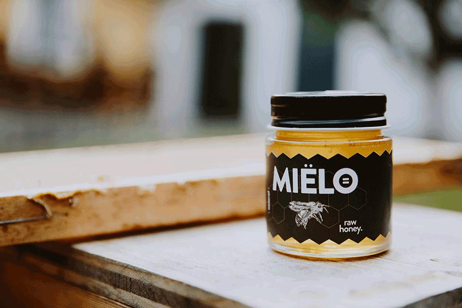 VONsociety: MIËLO Glas mit rohem Honig steht auf einem Holzbrett, im Hintergrund ist unscharf die Fassade eines Hauses zu sehen