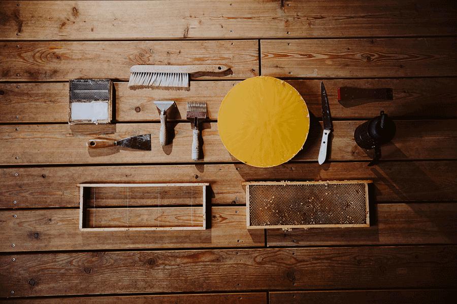 VOnsociety: Blick von oben auf Imkerwerkzeug, das auf einem Holztisch liegt