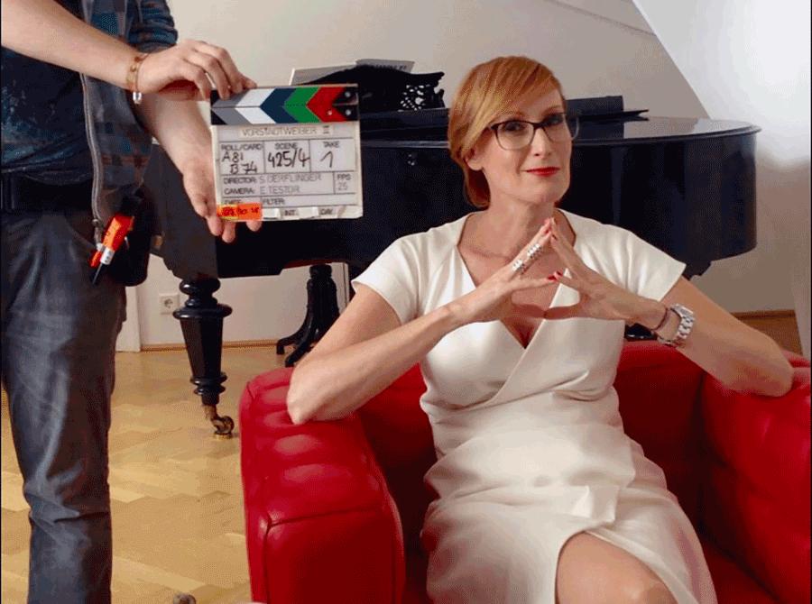 VONsociety: Schauspieler in der Krise, Nicole Beutler bei den Dreharbeiten zu Vorstadtweiber, sie trägt ein weißes kurzärmeliges Kleid, sitzt in einem roten Fauteuil, im Hintergrund ein schwarzer Stutzflügel, links halb im Bild ein Crew-Mitarbeiter mit der Filmklappe