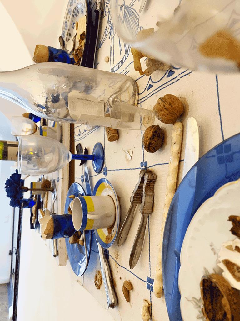 VONsociety: Close up eines Fallenbilds von Daniel Spoerri. Auf der an der Wand hängenden Tischplatte sind die Teile abgegessenen Tischs zu sehen. Blaue Eierbecher in denen die Eierschale steckt, leere weiße Glasflasche, Nussknacker und 2 Walnüsse, der Teil eines weißen Tellers auf dunkelblauem Platzteller, auf dem ebenfalls Nussschalen liegen