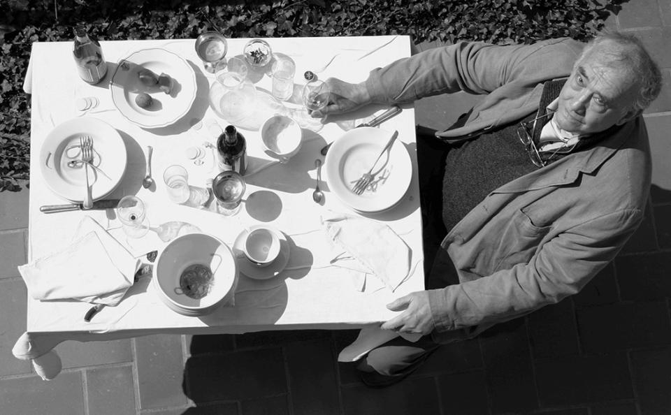 """VONsociety: schwarz-weiß Aufnahme von Daniel Spoerri aus der Vogelperspektive. Er sitzt auf einem Stuhl, hält eines seiner """"Fallenbilder"""" auf dem Schoß und blickt nach oben in die Kamera"""